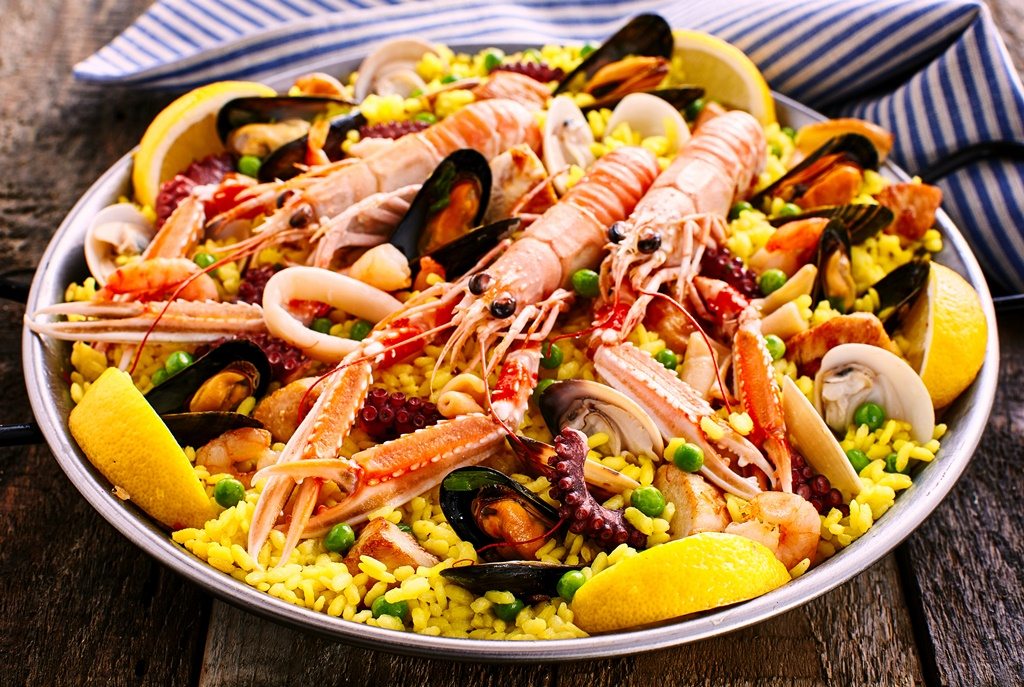 Close Up Overview of Colorful Spanish Seafood Paella Dish Served in Shallow Bowl with Blue and White Striped Linen Napkin on Rustic Wooden Table