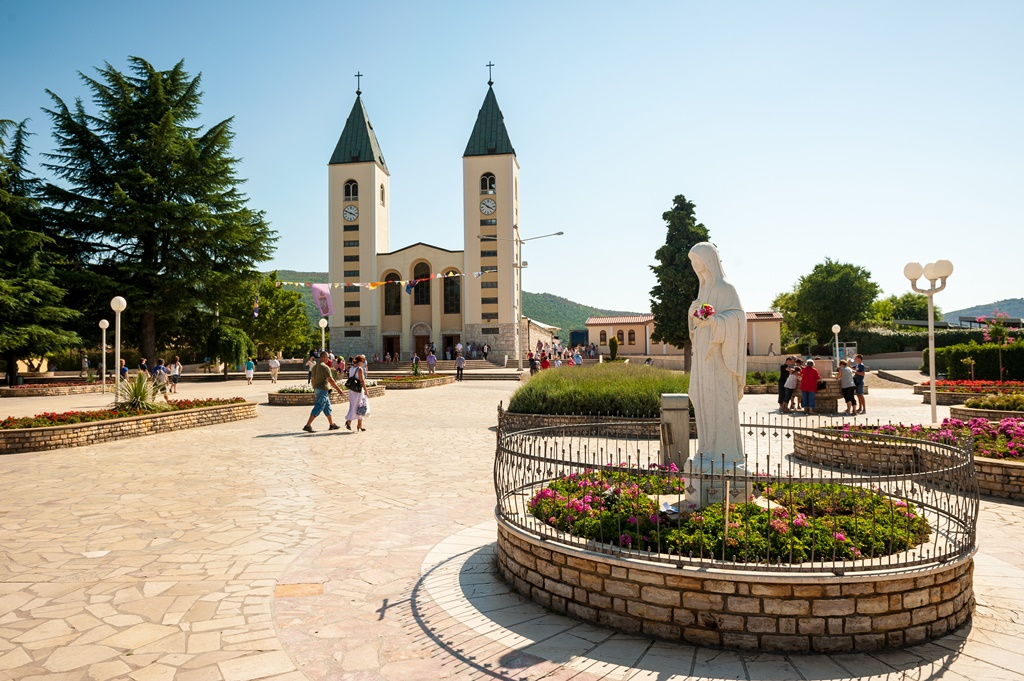 Medjugorje Sanctuary in Bosnia and Herzegovina. In the foreground is the vigin Mary statue and in the background is the parish church.