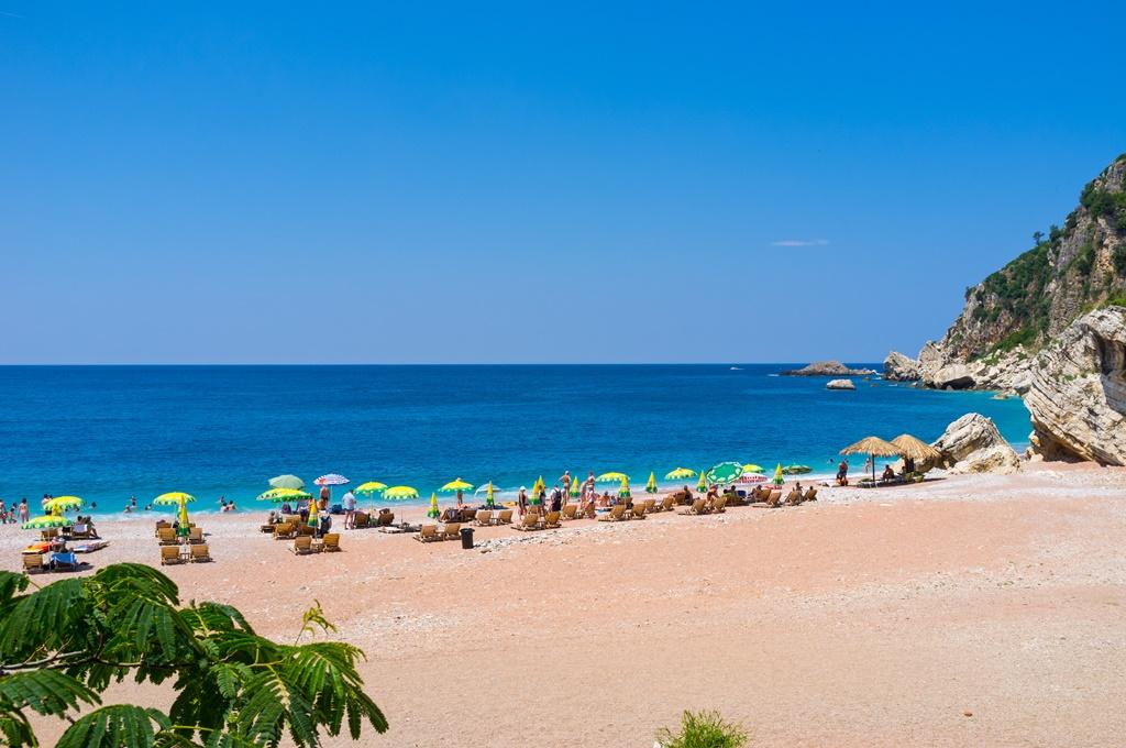 The cozy sand beach of Rezevici resort, located next to Petrovac on Budva riviera, Montenegro.