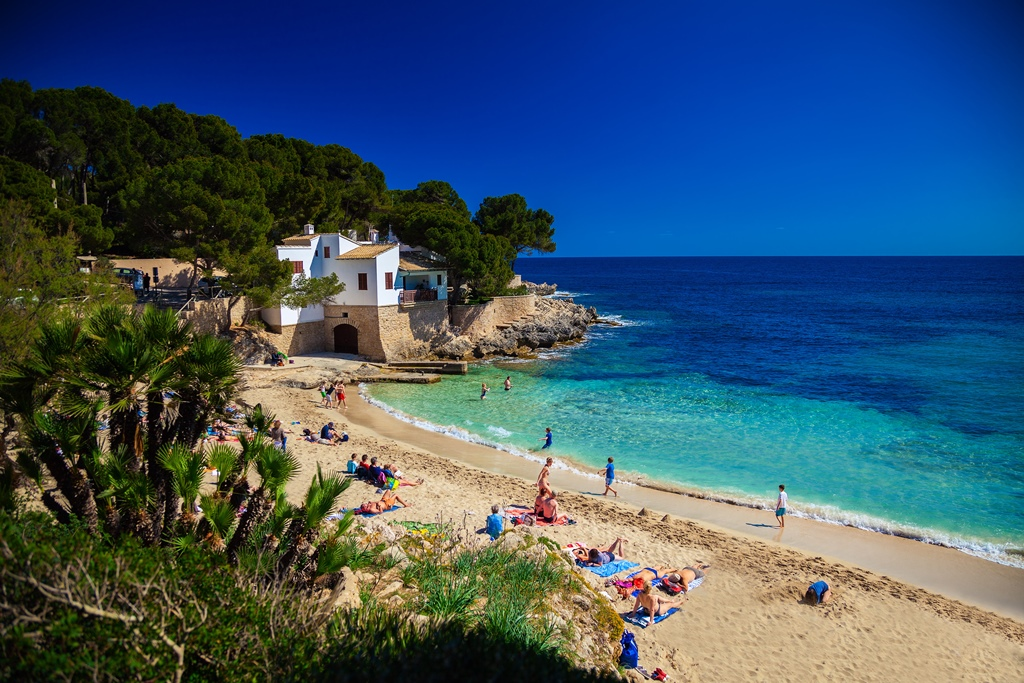 people enjoying the sun on the Cala Gat beach, Majorca, Spain