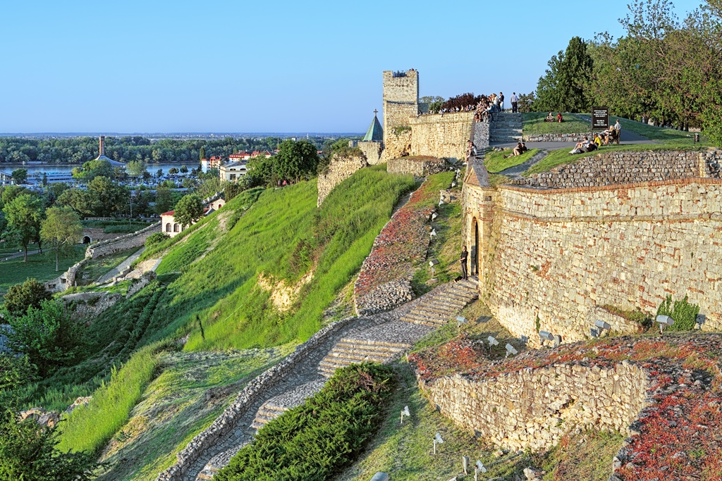 People sitting on the wall of the Kalemegdan fortress in Belgrade during sunset, Serbia