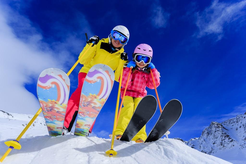 Ski, skiers, sun and winter fun - skiers enjoying ski vacation
